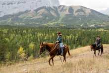 Young Couple Horseback Riding On Scenic Mountain Trail
