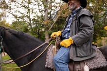 Happy Senior Male Rancher Horseback Riding On Black Horse