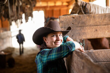 Portrait Happy Female Rancher In Cowboy Hat At Horse Stable Stall