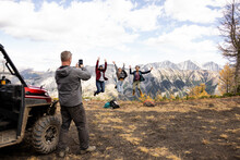 Guide Photographing Happy Female Hikers Celebrating At Mountain Summit