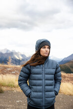 Young Female Hiker In Hooded Jacket In Mountains
