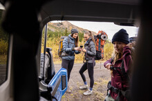 Young Women Friends With Backpacks Preparing For Hike At Back Of Jeep