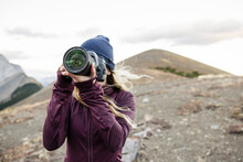 Young Female Photographer With Digital SLR Camera In Mountains