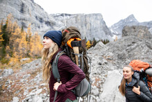 Young Women Friends Backpacking In Autumn Rocky Mountains, Canada