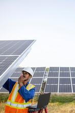 Technician Inspecting Solar Panels, Communicating On Walkie Talkie