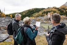 Trail Guide Helping Senior Bird Watchers In Autumn Mountain