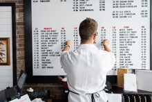 Man Altering Price List On Board In Shop