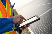 Close Up Of Technician Using Digital Tablet By Solar Panels