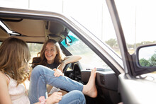 Happy Teenage Girl Friends Laughing Inside Sunny Car
