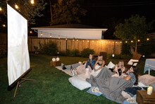 Teenage Girl Friends Watching Movie On Screen In Backyard At Night