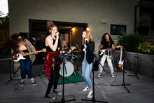 Teenage Girl Friends Singing And Practicing As Rock Band In Driveway
