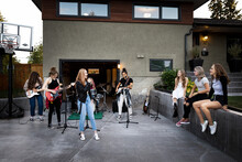Teenage Girl Friends Practicing Music As Rock Band In House Driveway