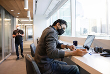 Businessman In Face Mask Working At Laptop In Highrise Office Window