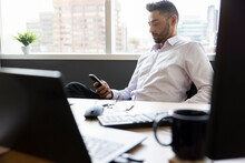 Businessman Using Smart Phone In Highrise Office