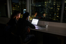 Business People Working Late At Laptop In Highrise Office Window