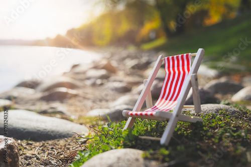 Fotografija red empty striped chaise longue on rocks by lake.