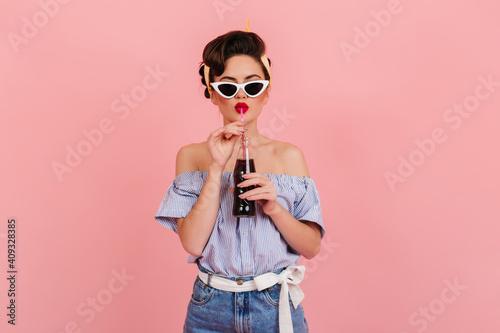 Fototapeta Wonderful pinup girl drinking beverage with pleasure