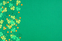 St Patricks Day Green Background With Shamrock And Gold Coin Confetti Side Border. Top Down View With Copy Space.