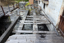 Old Broken Wooden Bridge With Gaps Over A Fast River