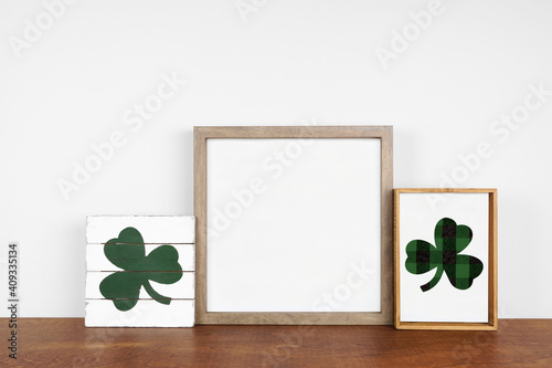 Obraz Mock up wood frame with St Patricks Day decor on a wood shelf. Rustic wood signs. Square frame against a white wall. Copy space. - fototapety do salonu