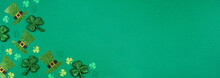 St Patricks Day Shamrock And Leprechaun Hat Corner Border. Overhead View Over A Green Paper Banner Background With Copy Space.