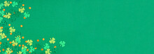 St Patricks Day Green Background With Shamrock And Gold Coin Confetti Corner Border. Overhead View Banner With Copy Space.