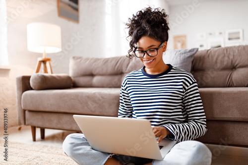 Obraz Joyful relaxed ethnic woman using laptop with interest at home - fototapety do salonu