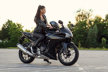 Stylish Beautiful Girl In Black Leather Jacket And Pants On Outdoors Parking Sits On Sports Motorcycle And Holds Protective Helmet.