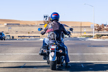 Back View Of Motorcyclist Waiting At A Traffic Light; American Flag Attached At The Back, Waiving In The Wind; San Francisco Bay Area, California