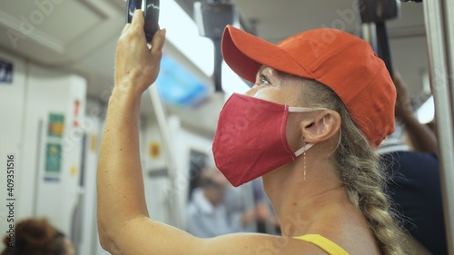 Fotografie, Tablou Woman travel caucasian ride at overground train airtrain with wearing protective medical red mask