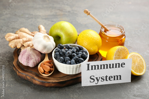 Card with phrase Immune System and fresh products on grey background