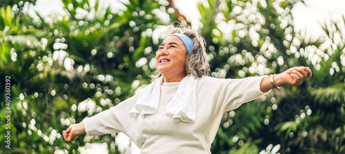 Fototapeta Portrait of happy senior old adult elderly asia women smiling standing and stretch her arms relax and enjoy with nature feeling breath fresh clean air in green park