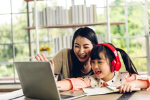 Mother And Asian Kid Little Girl Learning At Laptop Computer Making Homework Studying With Online Education E-learning System.children Video Conference Sey Hi With Teacher Tutor At Home