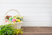 Colored Easter Eggs In The Basket And Spring Flowers On Wooden Background. Greeting Card