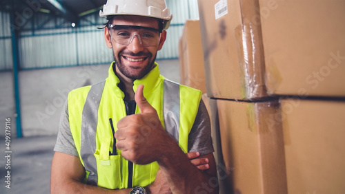 Professional industry worker close up portrait in the factory or warehouse . Production line operator or engineering looking at camera . © Blue Planet Studio