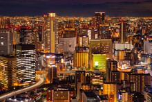 Evening In A Japanese City. Osaka Against A Dark Sky. Urban Landscape From A Height. Residential Areas Of Osaka. There Are Lights In The Windows Of The Houses Of The Japanese City. Life In Osaka.