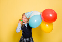 A Girl In A School Uniform And A Festive Cone On Her Head Holds Balloons In Her Hands And Blows A Pipe Isolated On A Yellow Background.