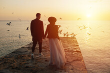 Back View Of Romantic Couple Holding Hands And Walking On The Beach At A Beautiful Sunset. Flying Seagulls On The Background.