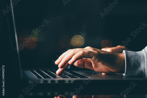 Freelance woman working on laptop at the night. Close up hand with laptop.