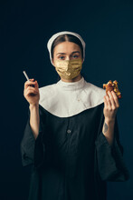 Medieval Young Woman As A Nun In Vintage Clothing And Golden Face Mask With Cigarette On Dark Blue Background. Concept Of Comparison Of Eras, Fashion, Ad, Healthcare. Royal Person Protected From Covid
