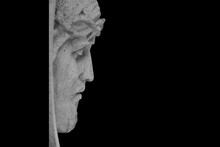 Face Of Jesus Christ In A Crown Of Thorns Against Black Background. Fragment Of An Ancient Statue. Profile Image.