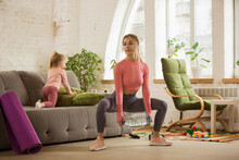Squats Using Bottle Like Dumbbells. Young Woman Exercising Fitness, Aerobic, Yoga At Home, Sporty Lifestyle. Getting Active With Her Child Playing, Home Gym. Healthcare, Movement, Motherhood Concept.
