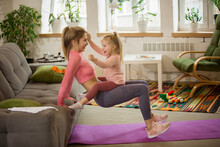 Squats With Daughter On Belly. Young Woman Exercising Fitness, Aerobic, Yoga At Home, Sporty Lifestyle. Getting Active With Her Child Playing, Home Gym. Healthcare, Movement, Motherhood Concept.