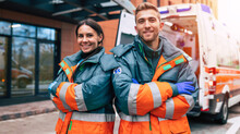 Two Confident Young Doctors Looking On The Camera On Ambulance And Hospital Background