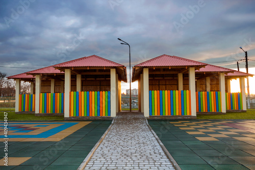 Fotografija Kindergarten playground with bright new alcove with multicolored low fence, big yard with soft rubber flooring on blue sky copy space background