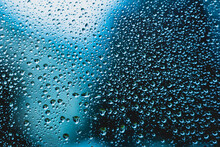 Water Droplets Background Texture On Window Macro Front View Blue Tint Backlit