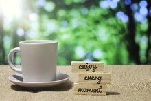 Selective Focus Image Of Wooden Tiles With Text ENJOY EVERY MOMENT And Cup Of Coffee. Bokeh Effect Background