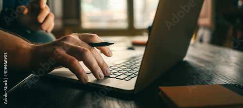Close-up of male hands with laptop. Man is working remotely at home. Freelancer at work