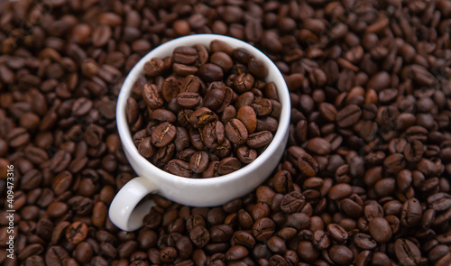White cup with coffee beans. Selective focus. © yanadjan
