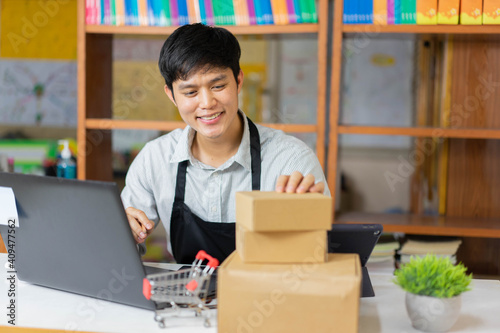Obraz close up young business owner sitting at home office on the table while checking detail of customer on boxes to delivery for SME and startup concept - fototapety do salonu
